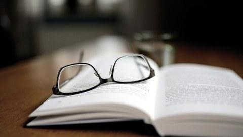 Auf einem aufgeschlagenen Buch liegt eine Brille