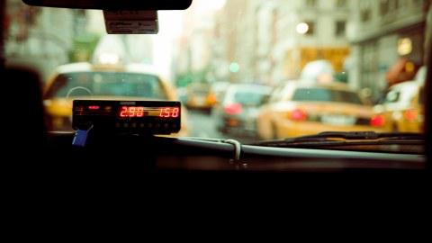 Foto des Innenraums eines Taxis mit Taxometer, man blickt durch die Frontscheibe auf eine start befahrene Straße