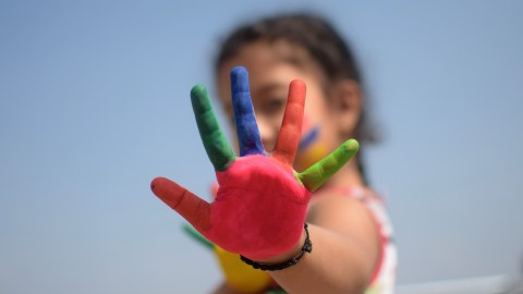 Ein Mädchen streckt seine bunt bemalte Handfläche in die Kamera