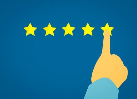 Eine Hand zeigt auf dem rechten von 5 gelben Sternen auf blauem Hintergrund