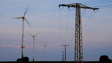 Am linken Bildrand sind Windräder zu sehen, am rechten ein Oberleitungsmast