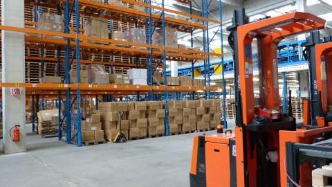 Blick in eine Lagerhalle: Rechts vorn im Bild steht ein orangefarbener Gabelstapler, im Hintergrund stehen deckenhohe, mit Kisten gefüllte Regale