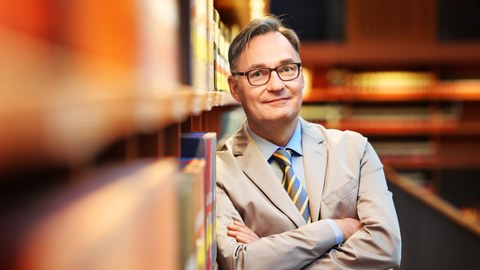 Prof. Bonte lehnt mit verschränkten Armen an einem mit Büchern gefüllten Regal, im Hintergrund sieht man verschwommen Bücherregale.