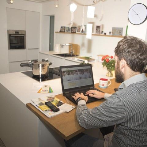 Junger Mann mit Bart sitzt in seiner Küche am Laptop und arbeitet