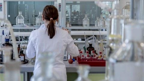 Man sieht eine junge Frau mit Zopf von hinten, die inmitten von chemischen Gerätschaften in einem Labor steht.