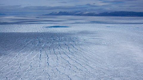 Eine große, rissige Eisfläche, im Hintergrund sind Berge und der Himmel zu sehen, alles in verschiedenen Schattierungen von Hellblau.