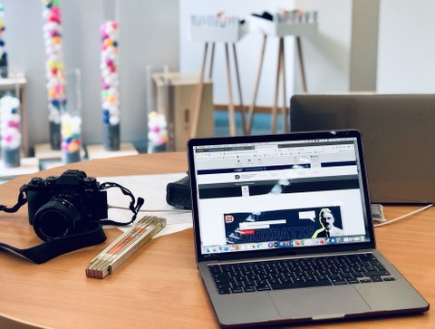 Ein aufgeklappter Laptop steht auf einem vollgestellten Schreibtisch.