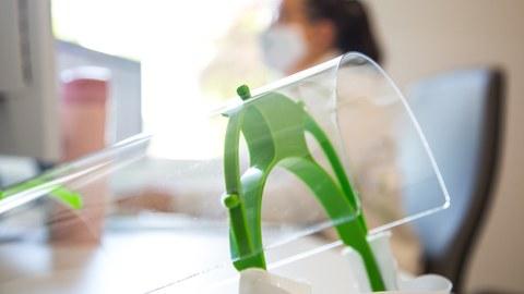 Eine Schutzmaske mit Visier liegt auf einem Schreibtisch, in Hintergrund ist eine Patientin mit Mundschutz