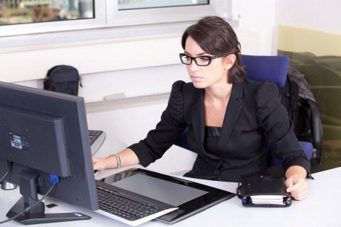 Junge, dunkelhaarige Frau mit Brille sitzt vor ihrem Computer und arbeitet