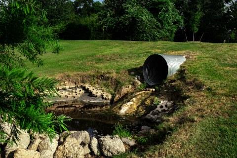 Ein Rohr liegt in einer Grube in einer Wiese