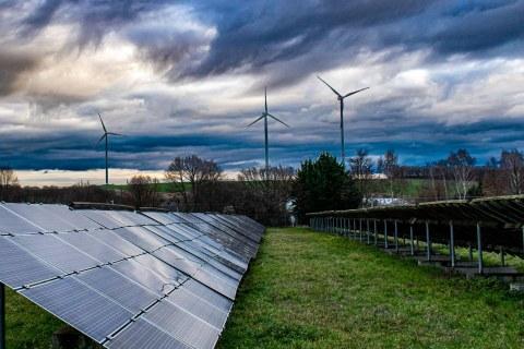 Solarpanele links auf einer Wiese, im Hintergrund sieht man ein Windrad vor bewölktem Himmel.