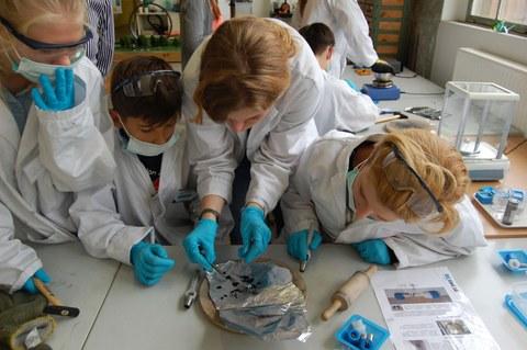 Jungs und Mädchen mit Mundschutz und Laborkittel experimentieren
