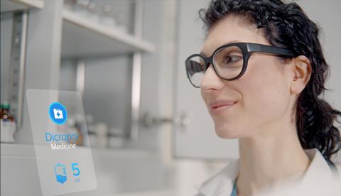 Eine dunkelhaarige junge Frau im rechten Bildrand trägt eine Brille mit dickem schwarzen Rahmen, im Hintergrund ist ein Labor zu sehen.