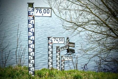 Wasserstandsmesser stehen auf einer Wiese vor einem Gewässer