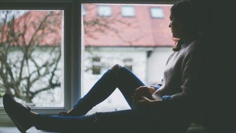 Junge Frau sitzt auf dem Fensterbrett und schaut aus dem Fenster