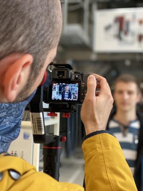 Fotoaufnahme über die Schulter eines Mannes, der eine Kamera bedient. Im Bildhintergrund sowie auf dem Display der Kamera ist ein weiterer Mann abgebildet.
