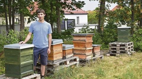 Kevin Günzel vor einem der zwei grünen Bienenkästen der TU Dresden.