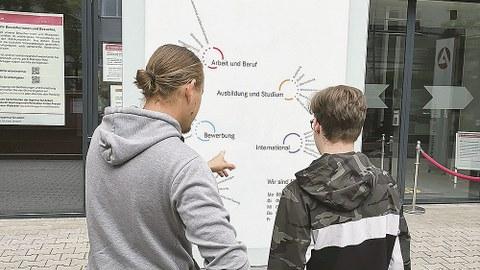 Hilfe bei der Orientierung – das Paten-Programm des Vereins. Ein Pate erklärt anhand eines Plakates, wie das Patenprogramm aufgebaut ist.