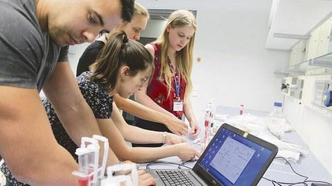 Vier Teilnehmende arbeiten in einem Labor und am Laptop.