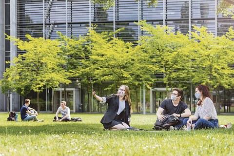 Drei Studierende mit Maske sitzen auf Wiese und machen ein Handy-Selfie.