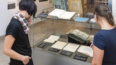 Zwei Besucherinnen betrachten eine Vitrine mit aufgeschlagenen Büchern.