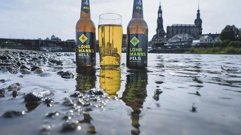 Zwei Lohrmanns-Bierflaschen und ein gefülltes Glas stehen im seichten Elbwasser vor der Stadtsilhouette Dresdens.