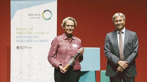 Prof. Ursula M. Staudinger hält den DRESDEN-concept-Staffelstab, den sie von ihrem Vorgänger Prof. Hans Müller-Steinhagen übergeben bekommen hat, in der Hand.