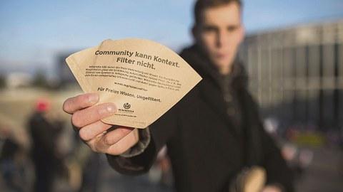 """Mann hält Kaffeefilter mit Aufschrift """"Community kann Kontext. Filter nicht."""" in der Hand."""