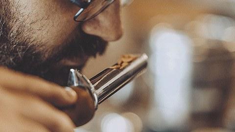 Ein Mann riecht an einer Schaufel Kaffeebohnen.
