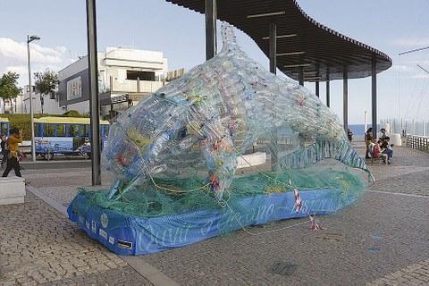 Überdimensionaler Delfin aus Plastikflaschen steht auf einer Uferpromenade.