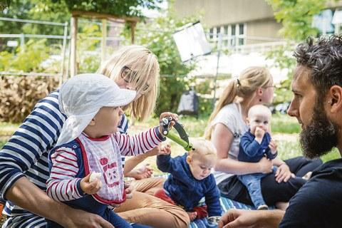 Kindergartenkinder sitzen mit Erwachsenen auf einer Wiese im Sommer.