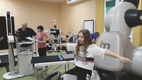 Ein Mädchen sitzt mit ausgebreiteten Armen auf einem großen Messgerät.