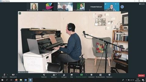 Screenshot des Konzertes, Adrian Zendeh sitzt mit Kopfhörern am Klavier.