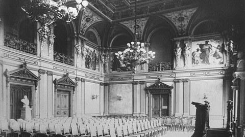 Schwarz-Weiß-Foto des bestuhlten Saals samt Rednerpult.