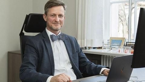Kanzler Dr. Andreas Handschuh sitzt am Schreibtisch.