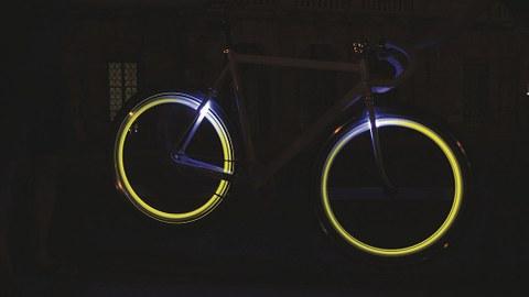 Fahrrad steht mit nachleuchtenden Reifen in der Dunkelheit.