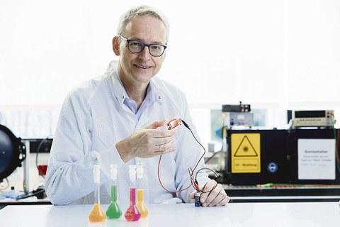 Prof. Leo sitzt an einem Labortisch. Im Hintergrund sind verschiedene Geräte zu sehen. Er hält eine Leuchtdiode in der Hand.