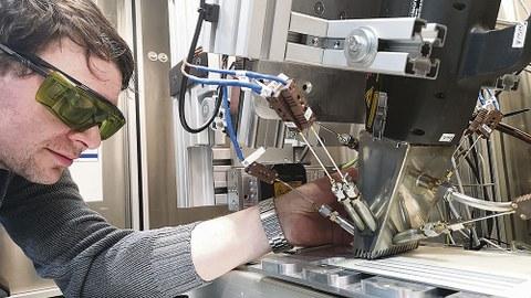 Techniker Erik Findeisen positioniert Thermoelemente an einem Laserkopf im Laserlabor des Instituts für Energietechnik an der TU Dresden. Darunter ist eine lackierte Probe zu sehen, die den Schutzanstrichen in alten Kernkraftwerken ähnelt.