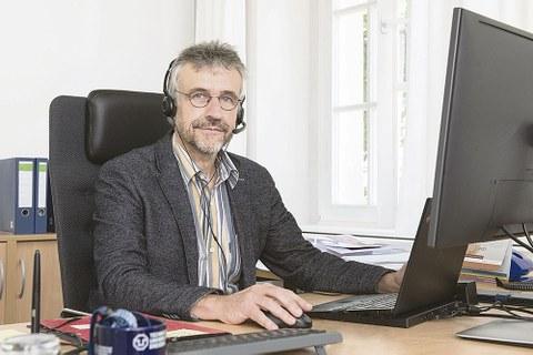 Prof. Kobel sitzt am Schreibtisch und schaut in die Kamera. Vor ihm steht ein aufgeklapptes Laptop, er hat Kopfhörer auf.