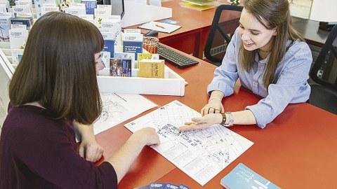 An einem Schreibtisch sitzen sich zwei Frauen gegenüber. Die eine erklärt der anderen den Campis-Plan der TUD.