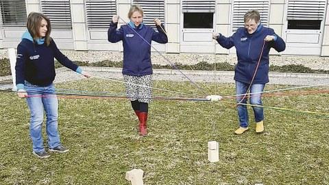 Drei Kolleginnen des DHSZ stehen auf einer Wiese. Sie probieren das Teamspiel »Tower of power« aus.