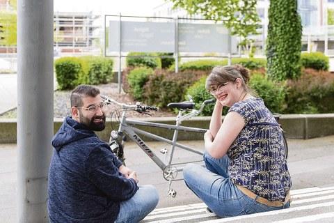 Franziska Götz und Mohamad Chaker sitzen auf Treppenstufen und haben sich zur Fotografin umgedreht.