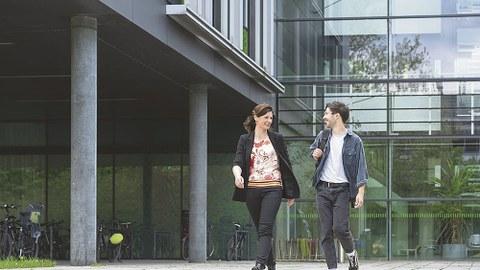 Ramona Nitzsche und Toni Blümel unterhalten sich im Gehen vor einem Gebäude.