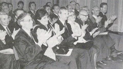 Auf dem SW-Foto sind besetzte Stuhlreihen in einem Saal zu sehen. In der ersten Reihe sitzen unter anderem Wissenschaftsminister Hans Joachim Meier, Rektor Prof. Günther Landgraf, Dresdens Oberbürgermeister Dr. Herbert Wagner und Kanzler Alfred Post.