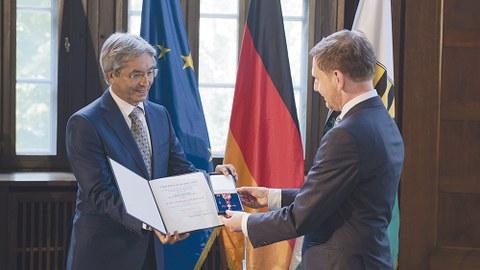 Sachsens Ministerpräsident Michael Kretschmer (r.) überreicht das Bundesverdienstkreuz und die Urkunde an Prof. Hans Müller-Steinhagen. Beide stehen vor den Flaggen Deutschlands, der EU und Sachsens.
