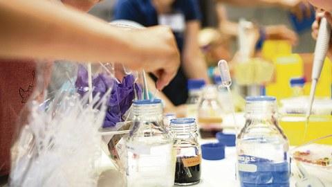 Glas-Laborbehältnisse stehen auf einem Tisch. Daraus werden von verschiedenen Menschen mit Pipetten Flüssigkeiten entnommen.