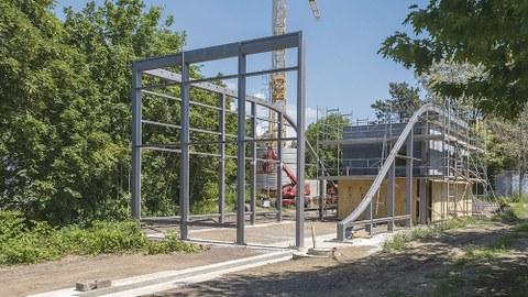 Die Stahl-Glas-Konstruktion steht auf dem Baugrundstück. Im Hintergrund rechts steht die zweisöckige BOX.