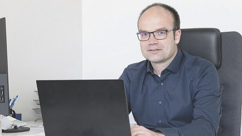 Prof. Lars Bernard sitzt am Schreibtisch. Vor ihm steht ein aufgeklapptes Laptop, auf dem er tippt. Prof. Bernard sieht den Betrachter an.