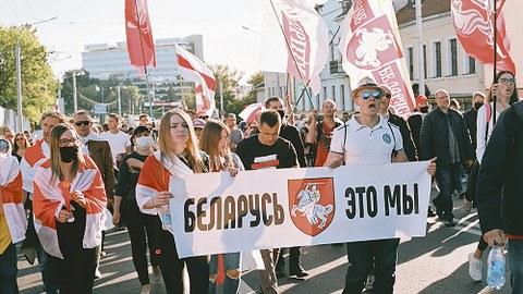 """Menschen mit rot-weißen Fahnen laufen in einem Demonstrationszug auf der Straße. Im Vordergrund tragen eine junge Frau und ein Mann ein Transparent, auf dem in kyrillischen Buchstaben """"Belarus, das sind wir"""" zu lesen ist."""