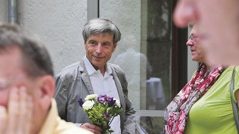 Dr. Lienert, im Gespräch mit einem nicht zu sehenden Gast, hält einen kleinen Blumenstrauß in der Hand.